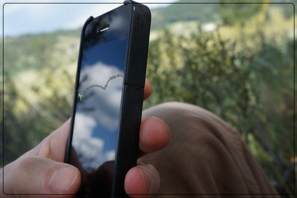 Sky and clouds reflected in Anthony Twig Wheeler's cell phone screen out in the meadow.