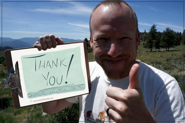 Holding a sign in the sun Anthony Twig Wheeler says thank you to people sharing feedback on his work