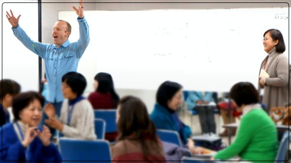 Arms reaching out smiling Anthony Twig Wheeler teaches in Japan.