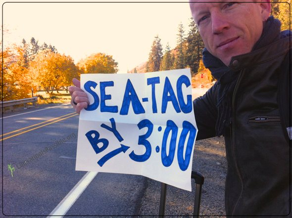 "Hitching a ride to Seattle Airport for another Adventure Anthony Twig Wheeler holds a sign saying ""Seat-Tac by 3"""